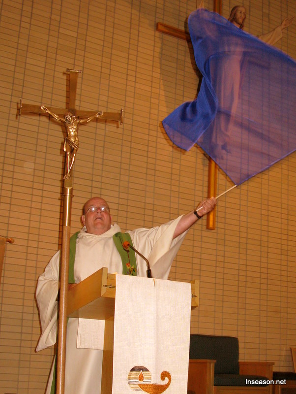Fr. Tom waving a banner at the podium at the Espousal Center in Waltham, MA